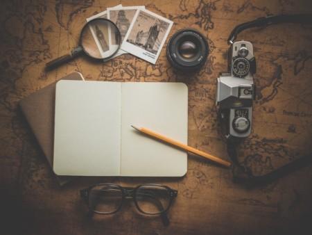 Kartta, suurennuslasi ja muistio pöydällä